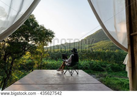 Freelancer Woman Working On Laptop During Vacation Holidays In Summer Among The Trees And Mountains.