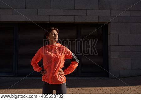 Active Millennial Girl Runner In Earphones Smartphone On Armband Train Workout On Street. Sporty Ton