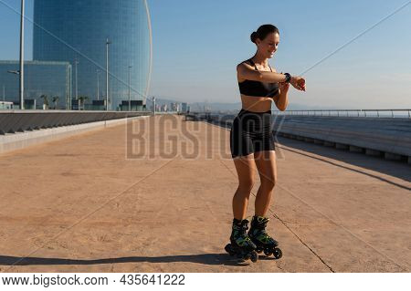 Full Body Glad Sportswoman Smiling And Checking Heart Rate On Smart Band While Riding Roller Blades