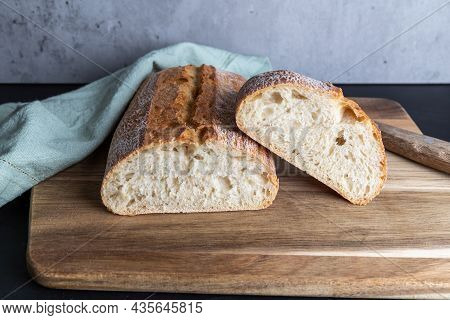 Fresh Ciabatta Cut In Half, Covered With A Kitchen Towel, Lies On The Wooden Board, Copy Space