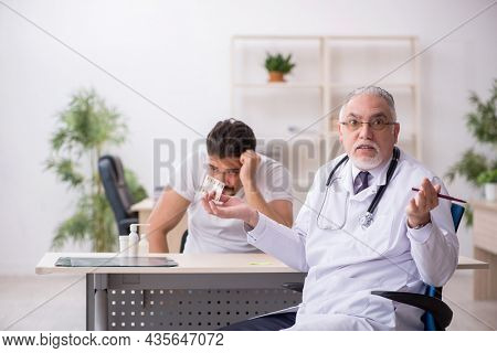 Old male doctor suggesting pills to young male patient