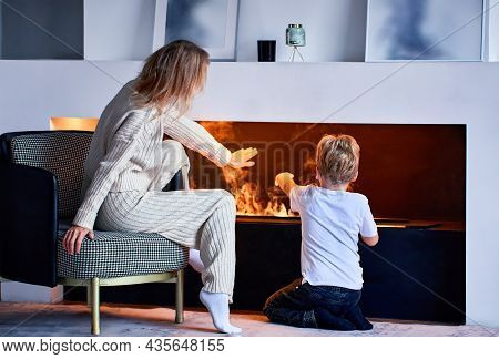 Woman Sits Near Fireplace With Little Boy In Living Room.
