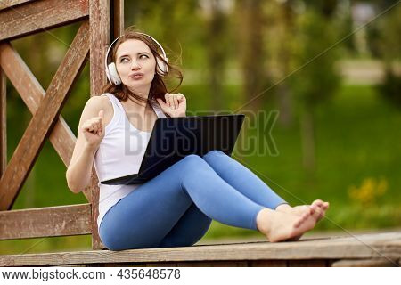 Grimacing Woman In Cordless Headphones With Laptop Sits On Nature.