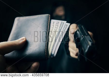 Armed Robbery. Mans Hand Holds Out Wallet Of Money To Robber With Gun. Hundred And Fifty Dollars In