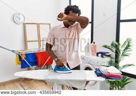 African man with curly hair ironing clothes at home smiling cheerful playing peek a boo with hands showing face. surprised and exited