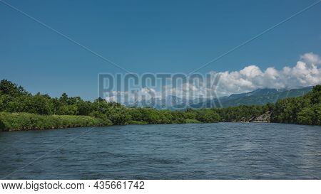 The Blue River Flows Peacefully. In The Distance, Inflatable Boats With People. On The Banks Of Lush
