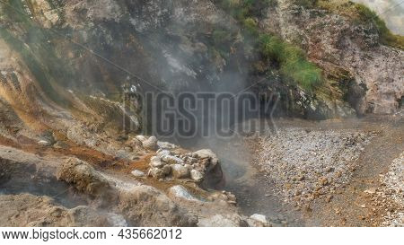 The Valley Of Geysers Is Shrouded In Steam From Hot Springs. The Slopes Of The Mountain Are Covered