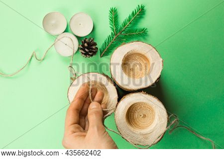 Diy Christmas Candle Holder Made Of Pine Logs, Candles, Craft Rope, Fir Branches And Cones. Hands Fa