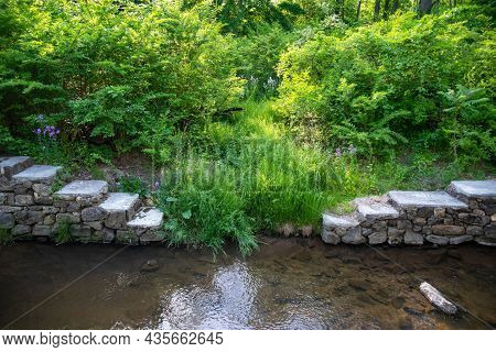 Beautiful Nature Scene Of Old Stone Steps Along A Calm Flowing Stream Channel With Green Foliage And