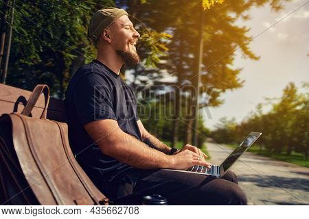 Outdoor Photo Of Laughing Millennial In Glasses Is Sitting On A Bench While Working At A Laptop Pc
