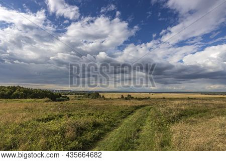 Road Through Fields. Country Road In Summer Field And Clouds On Blue Sky.