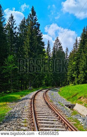 Railway Tracks In The Highlands Against The Blue Sky