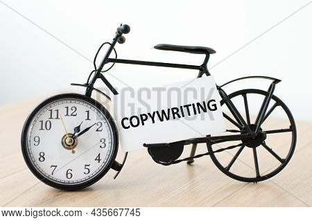 Copywriting Word On A White Card Next To A Clock On A Wooden Table On An Isolated Background