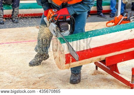 Man, A Participant In A Lumberjack Competition In Protective Overalls Nags A Tree Trunk With A Chain