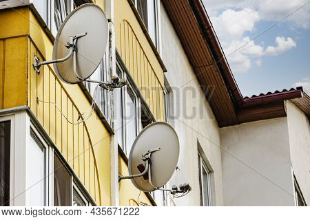 Satellite Dishes On The Facade Of A Multi-storey Residential Building. Satellite Tv And Communicatio