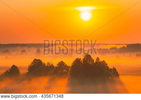 Amazing Sunrise Sunset Over Misty Landscape. Scenic View Of Foggy Morning Sky With Rising Sun Above