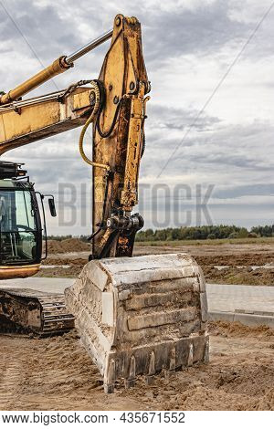 Heavy Crawler Excavator With A Large Bucket On The Background Of The Sunset Sky. Heavy Construction