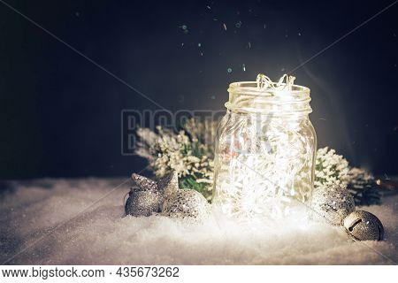 Christmas Decoration With Lights In The Jar, Fir Branch And Balls On Snow