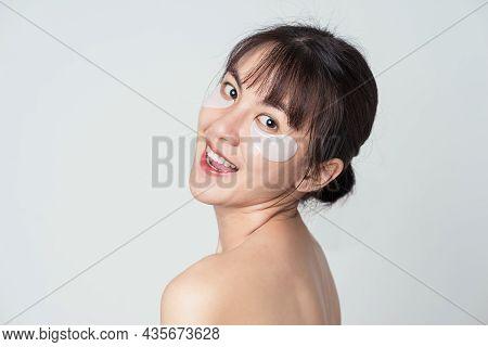 Joyful Asian Female Has Fresh Healthy Skin. Asian Woman Wear Collagen Patches Under Eyes. Concept Sk