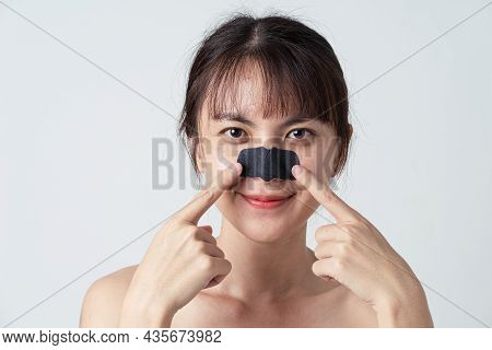 Beautiful Asian Female Model With Mask Charcoal Deep Cleansing Nose Pore Strip On Fresh Clean Skin.
