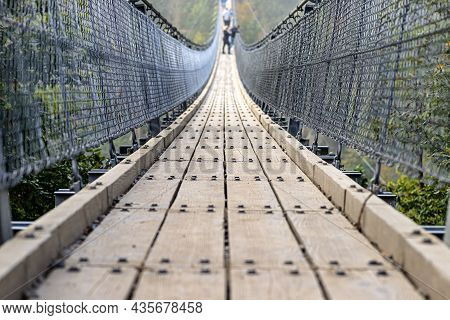Suspension Wooden Bridge With Steel Ropes Over A Dense Forest In West Germany, Close Up On A Wooden