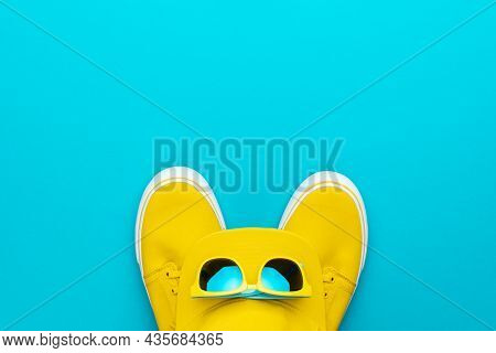Top View Photo Of Yellow Baseball Cap, Sunglasses And Sneakers As Summer Concept. Flat Lay Image Of