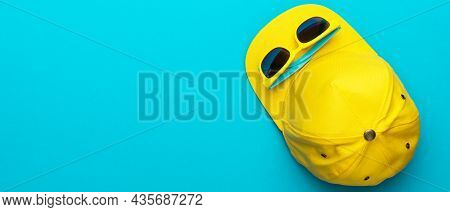 Top View Photo Of Yellow Baseball Cap And Sunglasses As Summer Concept. Flat Lay Image Of Summertime