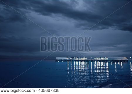 Twilight Landscape Of Pier Stretching Out Into Sea. Cloudy Sky. Illumination And Umbrellas On Ocean