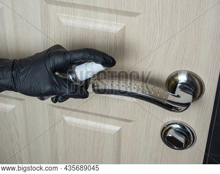 A Man In Black Latex Gloves Sprays Antiseptic On The Door Handle. Processing Items To Reduce The Cha