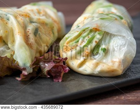 On A Black Textured Plate Are Rolled Up Spring Rolls. A Delicious Diet Dish. Asian Cuisine, Close Up