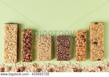 Various Energy Protein Bars With Ingredients On Green Background. Healthy Granola Bars. Space For Te