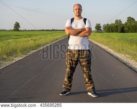 A Middle-aged Man With A Backpack On His Back Is Facing The Camera On The Road In The Field. His Han