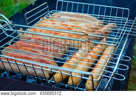 Close-up Of Sausages On The Grill Are Fried On The Grill. Delicious Juicy Chicken Sausages. Picnic