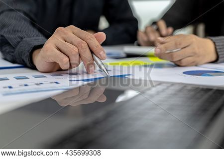 Business Men Are Looking At The Company's Financial Documents To Analyze Problems And Find Solutions