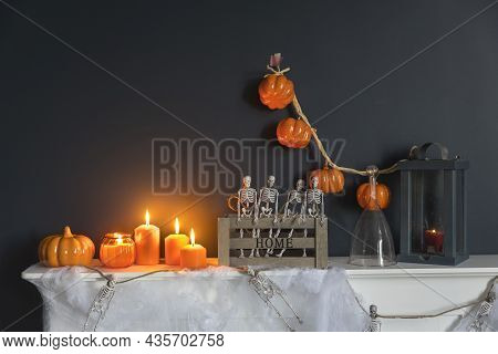 Halloween Home Decoration. Plastic Toy Skeletons In A Wooden Box On A Fireplace Against A Dark Blue