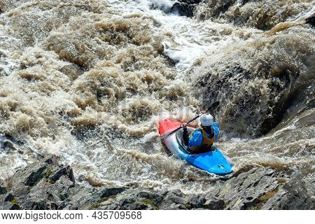 Dangerous Kayaking On A Mountain Stormy River. Man In A Boat On A Mountain River Strive Down Into Th