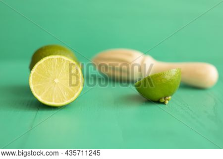 Lime With A Wooden Hand Press On A Textured Turquoise Background. There Is A Place For Text