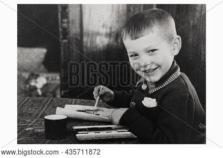 Retro Portrait Of Smiling Soviet Boy Drawing With Paints On Paper. Vintage Black And White Paper Pho