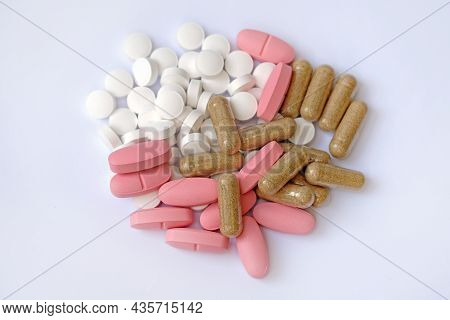 White Round Tablets, Pink Oval Tablets And Capsules On A White Background. Food Supplements In The F