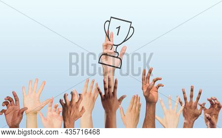 Hand Of Young European Man With Winners Cup, Trophy And Many Multiracial Hands Reaching For It