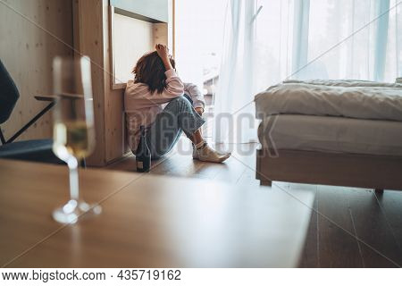 Wine Glass On The Table With The Unfocused Sad Woman Sitting On The Floor In The Bedroom With A Bott
