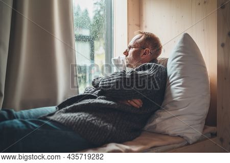 Sleeping Middle-aged Man In Eyeglasses Dressed Open Cardigan Lying On Cozy Bed Pillow Next To Window