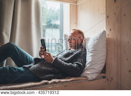 Window Glass With Raindrops Photo With A Middle-aged Man Dressed Warm Knitted Cardigan Lying On The
