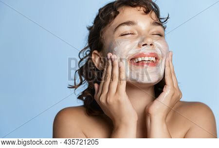 Cosmetic Procedure And Daily Care. Beautiful Laughing Model Washing Face With Facial Mask, Applying