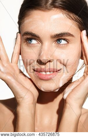 Vertical Portrait Of Young Woman Washing Her Face With Cleansing Foam Gel, Smiling Happy, Cleaning H