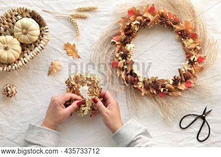 Hands Making Dried Floral Wreath From Dry Pampas Grass And Autumn Leaves. Flat Lay On Off White Text