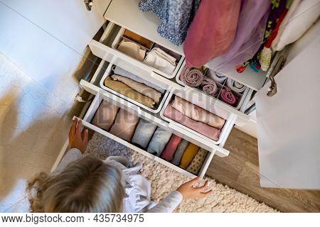 Female Hands Organizing Storage Of Underwear Socks T Shirts Use Marie Kondos Method. Perfectionist T
