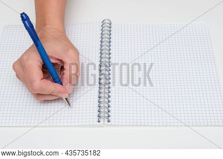 Writing Notes Or Planning A Schedule On Blank Spiral Notebook, Hand Using A Pen On A Checkered Blank