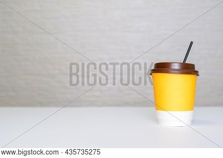 A Yellow Paper Disposable Takeout Coffee Cup With A Brown Cap And A Straw On White Background Agains