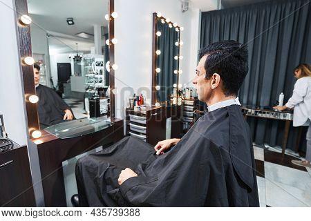 Male Visitor Of Barbershop Sitting Before Mirror